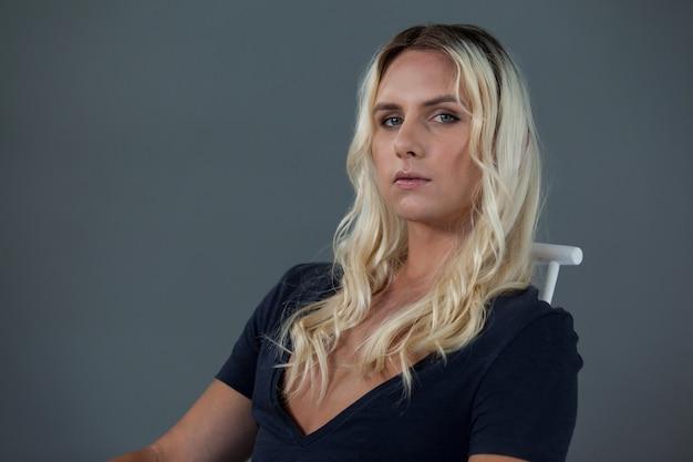 Porträt der schönen transgenderfrau, die auf stuhl sitzt