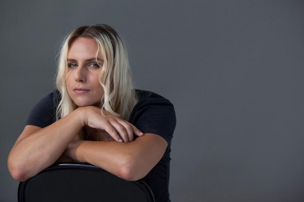 Porträt der schönen transgenderfrau, die sich auf stuhl stützt