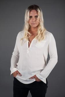 Porträt der schönen transgenderfrau mit den händen in den taschen