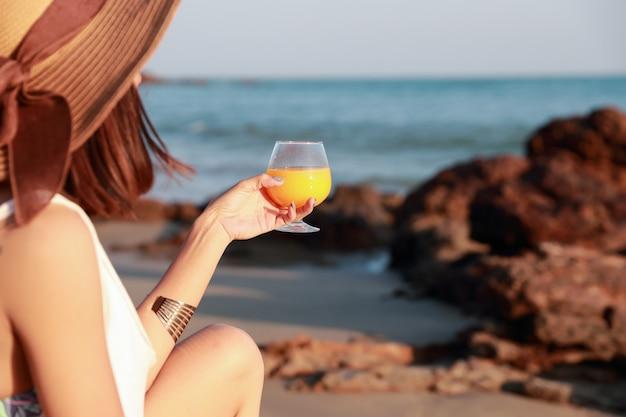 Porträt der schönen und glückfrau genießen feiertagsferien mit orangensaft auf dem strand