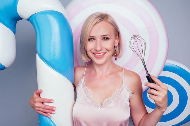 Porträt der schönen und jungen blonden frau sexy model konditor perfekte make-up halten einen schneebesen und lutscher gefälschte süßigkeiten, süßigkeiten hintergrund im studio. konzept der ake-küche und konditorei.