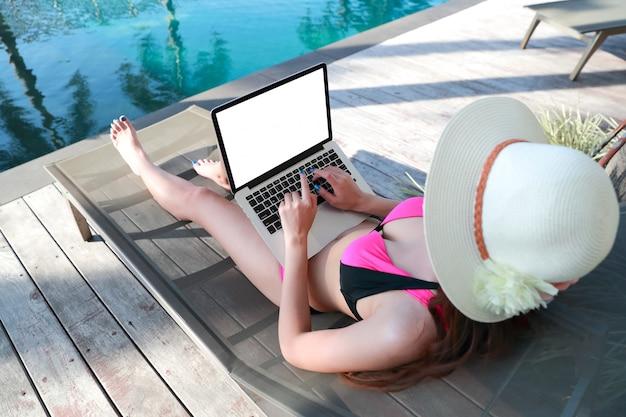 Porträt der schönen und sexy frau, die laptop-computer nahe swimmingpool verwendet