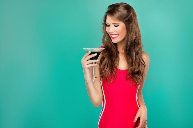 Porträt der schönen verführerischen sexy frau trinkt sommercocktail auf grünem hintergrund