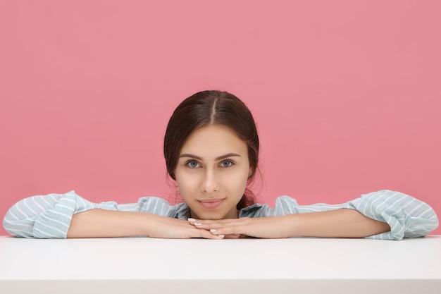 Porträt der schönen verspielten jungen kaukasischen frau, die ellbogen auf weißen tisch mit freudigem lächeln setzt. hübsches mädchen, das gegen leere rosa kopyspacewand aufwirft