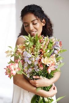 Porträt der schönen zarten afrikanischen frau im weißen kleid lächelnd, das blumenstrauß hält. geschlossene augen.