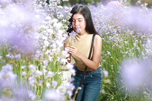 Porträt der schönheit eine glückliche zeit habend und unter blume naga-mit haube feld in der natur genießend