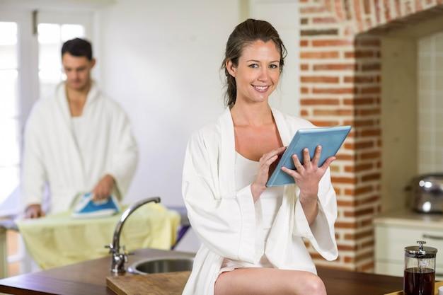 Porträt der schönheit im bademantel, der auf küchenarbeitsplatte sitzt und digitale tablette verwendet, während bügelnde kleidung des mannes hinter ihr