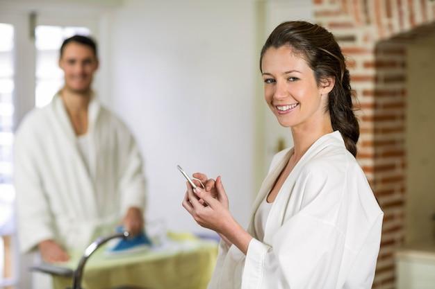 Porträt der schönheit im bademantel, der auf küchenarbeitsplatte sitzt und eine textnachricht auf smartphone schreibt, während bügelnde kleidung des mannes hinter ihr