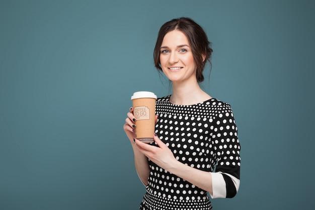Porträt der schönheit in der gesprenkelten kleidung, die mit coffe in den händen steht