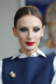 Porträt der schönheit mit hellem bilden und rote lippen im weißen hemd mit ärmelloser jacke