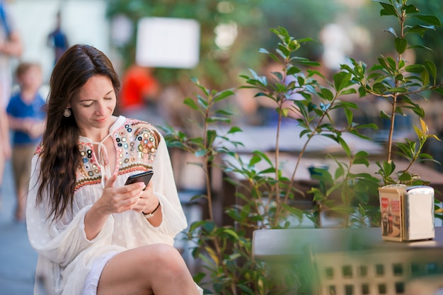 Porträt der schönheit sitzend in trinkendem kaffee des cafés im freien und smartphone verwendend.