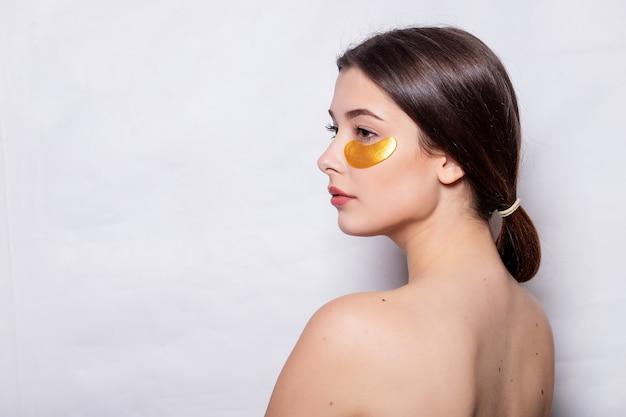 Porträt der schönheits-frau mit augenklappen. frauen-schönheits-gesicht mit maske unter augen. schöne frau mit natürlichem make-up und goldkosmetik-kollagen-patches auf frischer gesichtshaut