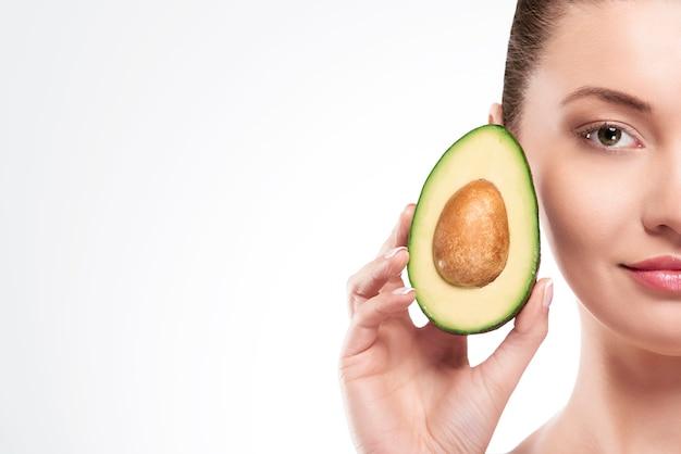 Porträt der schönheitsfrau mit avocado