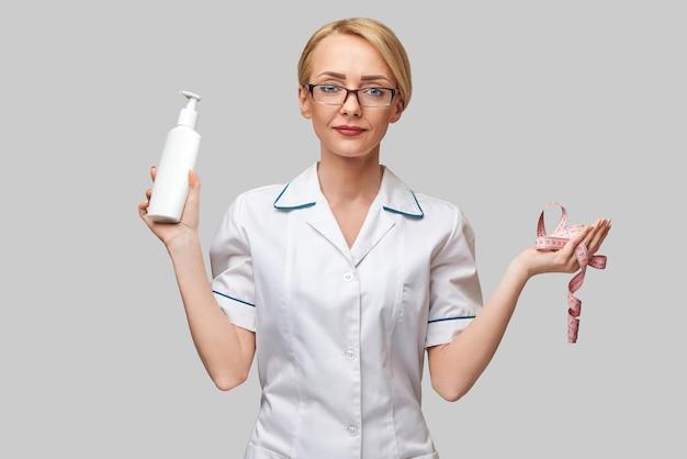 Porträt der schönheitsspezialistin, die in ihrer handflasche körperlotion und maßband hält.