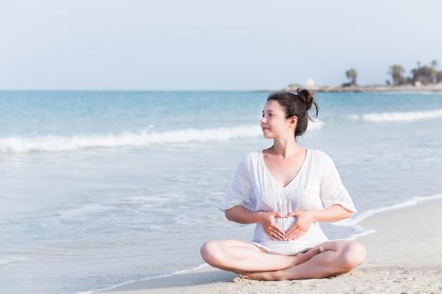 Porträt der schwangeren frau am strand mit weißem sand