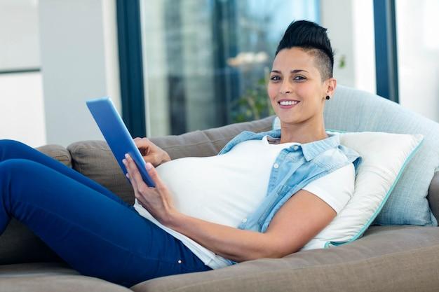 Porträt der schwangeren frau, die digitale tablette bei der entspannung auf sofa im wohnzimmer verwendet