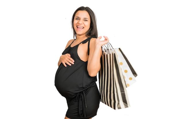 Porträt der schwangeren frau, die einkaufstaschen gegen weiße wand hält. einkaufskonzept.