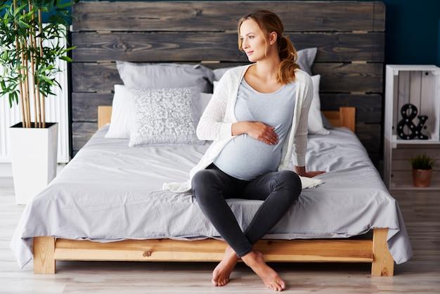 Porträt der schwangeren frau, die im schlafzimmer stillsteht