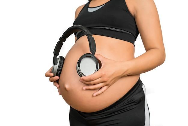 Porträt der schwangeren frau, die kopfhörer auf bauch hält