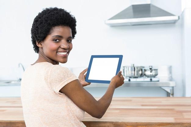 Porträt der schwangeren frau, die zu hause digitale tablette in der küche verwendet