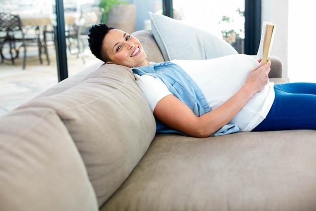 Porträt der schwangeren frau ein buch beim lügen lesend auf sofa im wohnzimmer