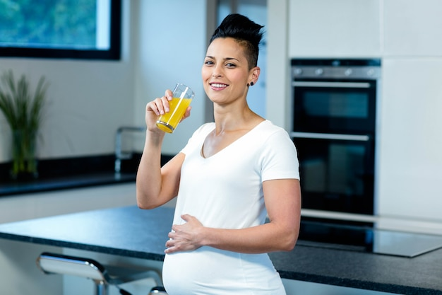 Porträt der schwangeren frau ihren bauch beim trinken des safts in der küche berührend