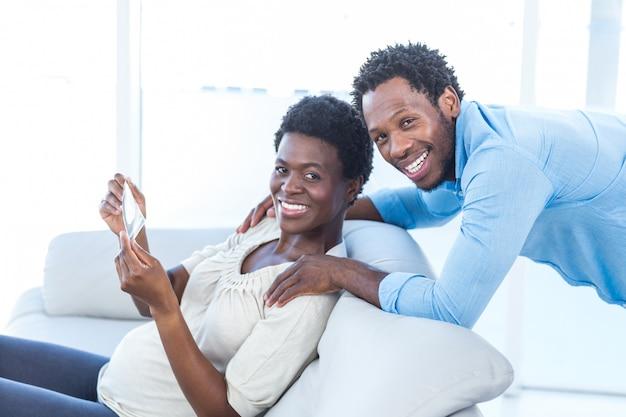 Porträt der schwangeren frau mit dem ehemann, der foto beim zu hause sitzen hält