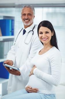 Porträt der schwangeren frau mit doktor in der klinik