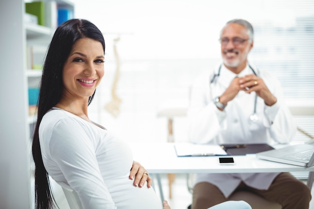 Porträt der schwangeren frau sitzend mit doktor an der klinik für gesundheitsüberprüfung