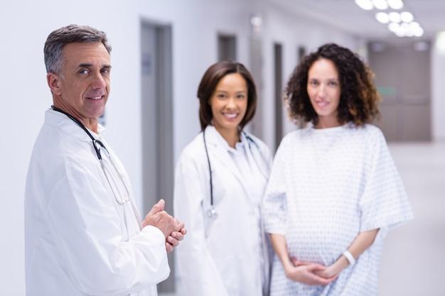 Porträt der schwangeren frau und der ärzte, die im korridor stehen