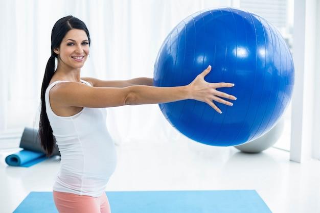 Porträt der schwangeren frau zu hause trainierend mit übungsball