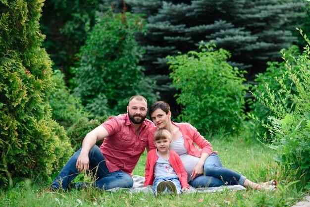 Porträt der schwangeren hübschen frau mit ihrem jungen ehemann und kleinen netten kind, die in park umarmen und gehen.