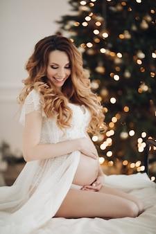 Porträt der schwangeren kaukasischen frau wirft für die kamera im weißen kleid im schlafzimmer nahe dem weihnachtsbaum auf