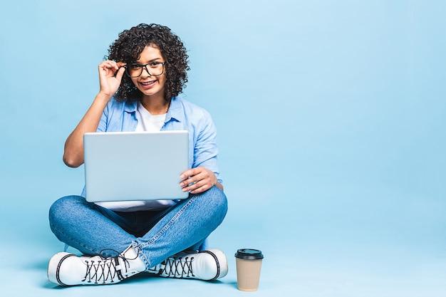 Porträt der schwarzen afroamerikanerfrau im lässigen sitzen auf boden in der lotushaltung und im halten des laptop lokalisiert über blauem hintergrund