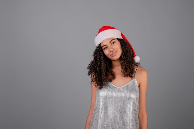 Porträt der schwarzen frau silbernes kleid und weihnachtshut tragend lokalisiert über grau