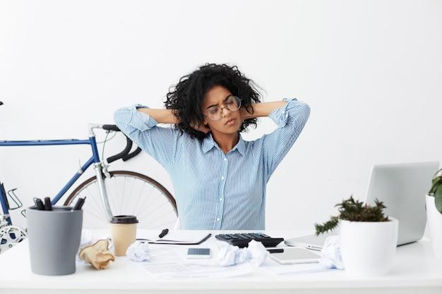 Porträt der schwarzen studentin, die arme streckt, die nach beendigung ihrer hausaufgaben müde sind