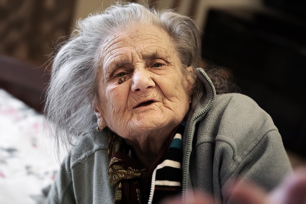 Porträt der sehr alten müden frau in der depression, die drinnen auf dem bett sitzt