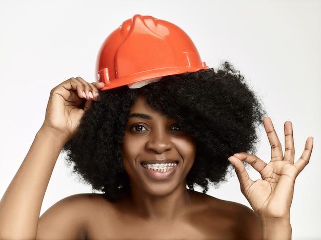 Porträt der selbstbewussten arbeiterin im orangefarbenen helm