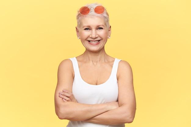 Porträt der selbstbewussten frau mittleren alters mit gebräuntem sportlichem körper, der heißes sonniges wetter genießt, das kamera mit glücklichem lächeln betrachtet, arme auf ihrer brust kreuzend, weißes trägershirt und sonnenbrille tragend