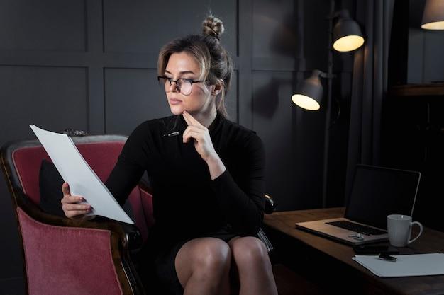 Porträt der selbstbewussten geschäftsfrau, die papiere prüft