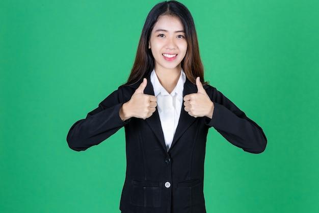 Porträt der selbstbewussten jungen asiatischen geschäftsfrau, die daumen aufgibt