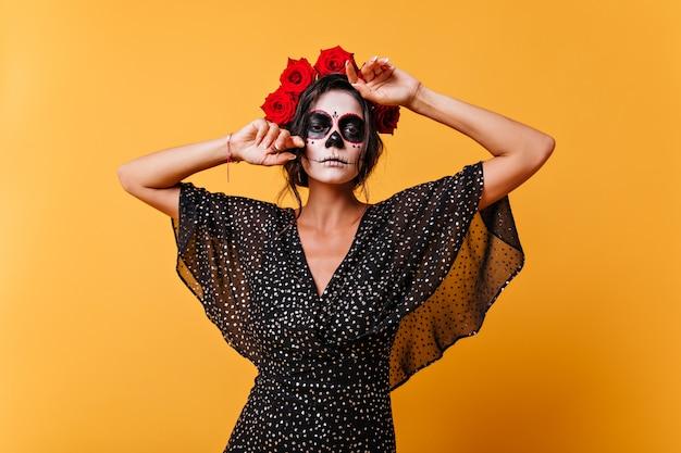 Porträt der selbstbewussten lateinamerikanischen frau mit make-up für halloween, das in ihrem schwarzen kleid aufwirft