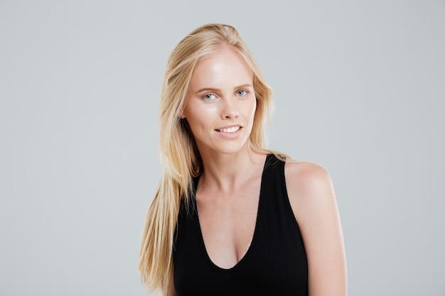 Porträt der selbstbewussten schönen jungen frau mit blondem haar über weißem hintergrund