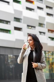 Porträt der selbstvertrauengeschäftsfrau mit dem kaffee, zum nahe bei dem büro zu gehen.