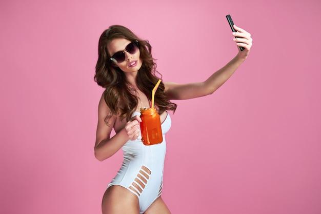 Porträt der sexy frau im weißen badeanzug-monokini, der sonnenbrille hält, die getränk hält und selfie-schuss auf rosa wand tut