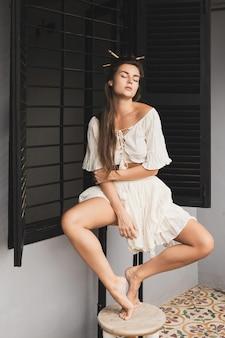 Porträt der sexy frau mit stilvoller frisur, die natürliche stoffkleidung trägt