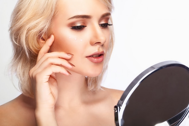 Porträt der sexy jungen frau mit der frischen gesunden haut, die zuhause im spiegel schaut.