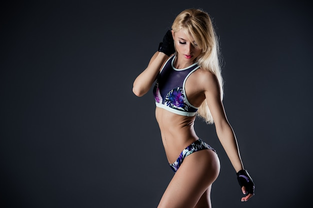 Porträt der sexy jungen frau mit ihren händen auf den hüften, die kamera betrachten. fitness-frau mit muskulösem körper bereit handhandschuhe für training auf grau