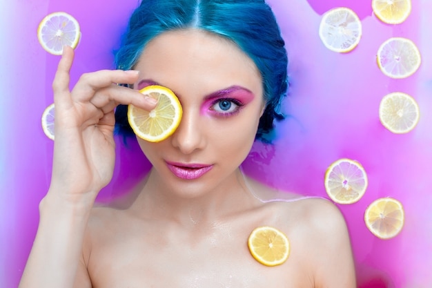 Porträt der sexy luxusfrau der jungen mode mit dem blauen haar, das in der badewanne sich entspannt.