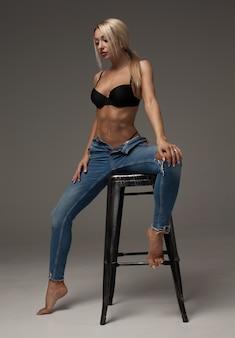 Porträt der sexy schönen blondine mit großer figur, die blaue markenjeans trägt, die uns ihren verlockenden bauch zeigen. auf grauem hintergrund isoliert